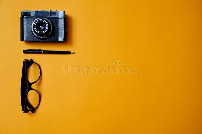 Blogging, blog and blogger or social media concept: glasses, photo camera and a pen on the yellow background. Flat lay.  stock photos