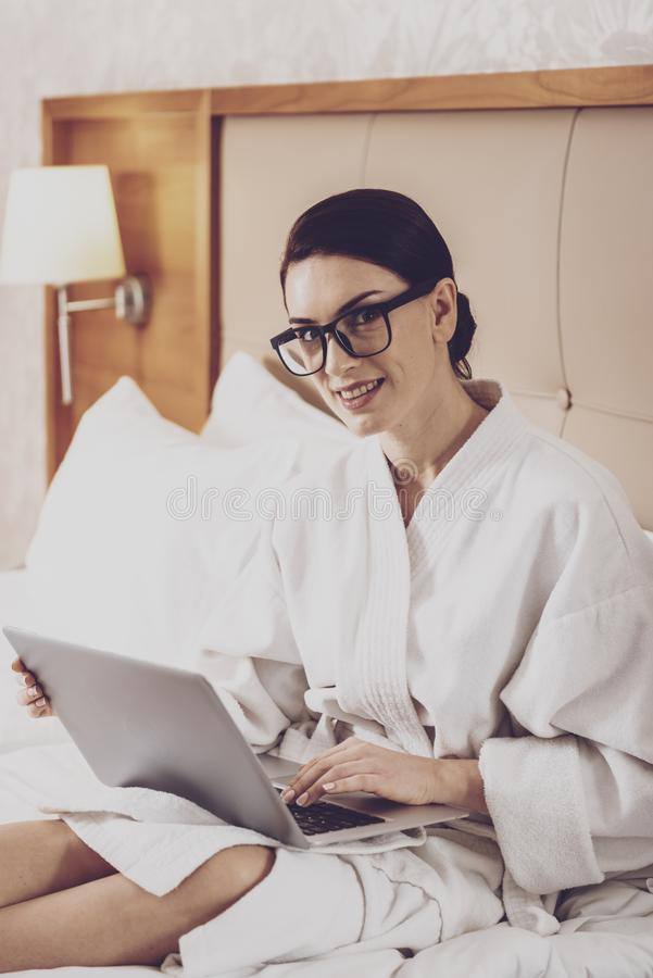 Delighted housewife communicating via social networks. Blogging. Delighted joyful housewife in bathrobe holding a laptop while communicating via social networks stock images