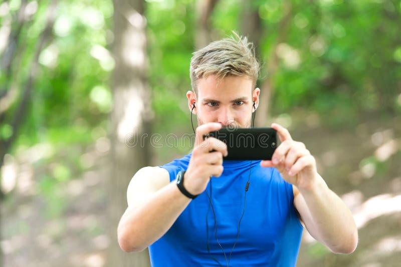 Blogging gadżet w nowożytnym sporcie mięśniowy mężczyzna w tropicielu robi fotografii sporta app na telefonie cyfrowy sport M?drz obrazy royalty free