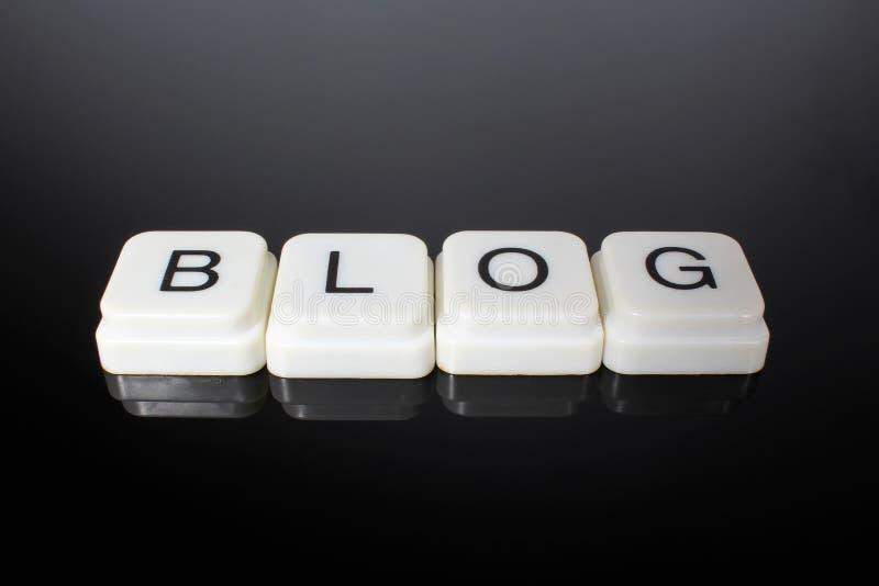 Blogtextwort-Titeltitel-Aufkleberabdeckungs-Hintergrundhintergrund Alphabetbuchstabebauklötze auf schwarzem reflektierendem Hinte stockbilder