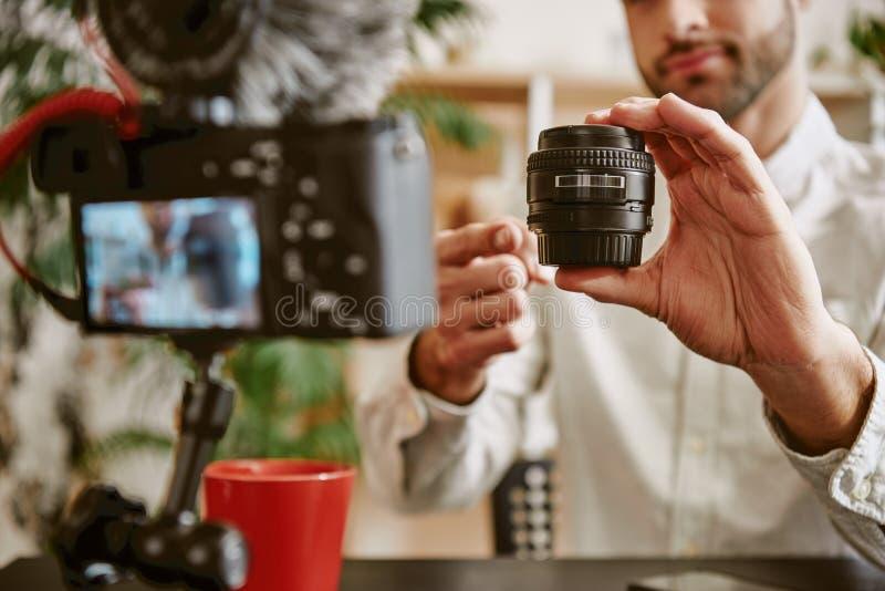 Blogue da tecnologia Foto ascendente próxima das mãos do blogger que mostram a objetiva em linha e que falam sobre suas vantagens fotos de stock royalty free