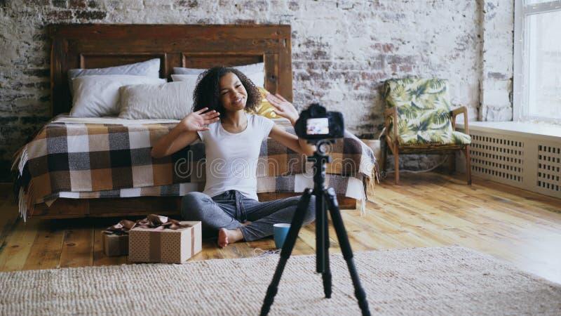 Blogue video da gravação alegre nova da menina da raça misturada sobre a caixa de presente do Natal da embalagem em casa imagens de stock