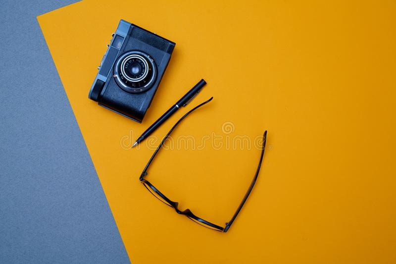 Bloguer, blog et blogger ou concept social de médias : verres, caméra de photo et un stylo sur le fond jaune Configuration plate image stock