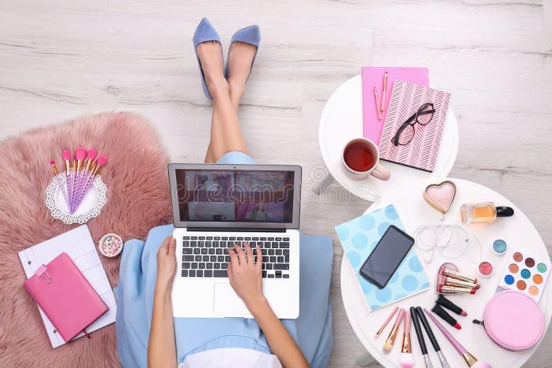 Bloguero con ordenador portátil y cosméticos sentados en el suelo, vista superior imagen de archivo libre de regalías