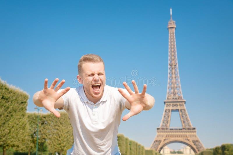 Bloguero masculino activista de derechos humanos muestra una señal de cese a la migración de personas a Europa, Torre Eiffel, Par fotografía de archivo libre de regalías