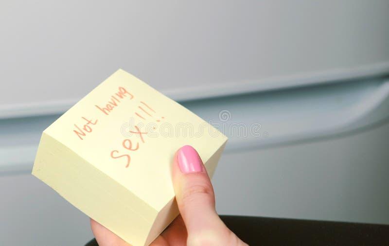 Blok żółty majcheru papieru prześcieradło z słowami no ma płci w kobiety ` s ręce obraz royalty free