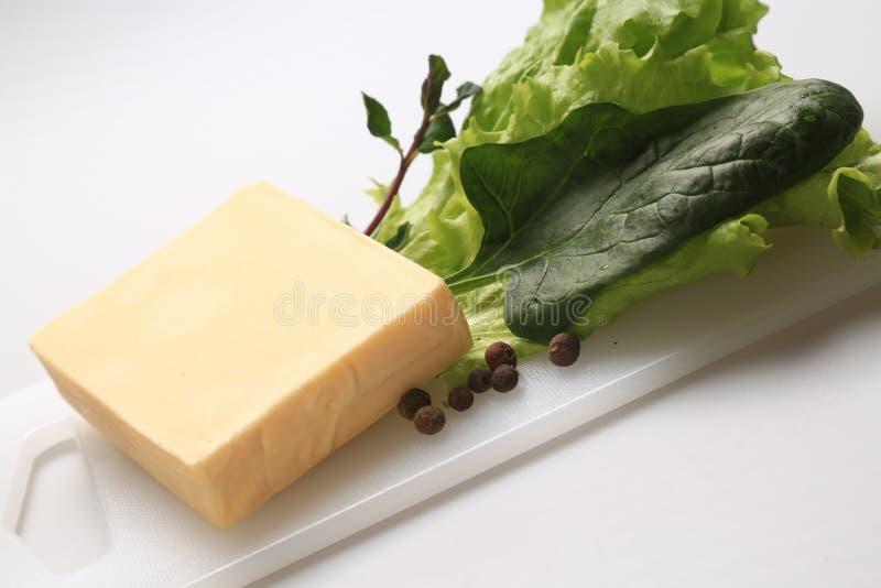 Blok żółty ser z niektóre szpinakami na stronie obrazy stock