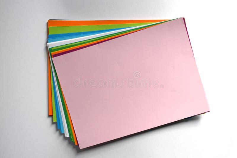 Blok barwiony A4 ciąć na arkusze na białym tle, menchia barwi iluminuje słońcem fotografia stock