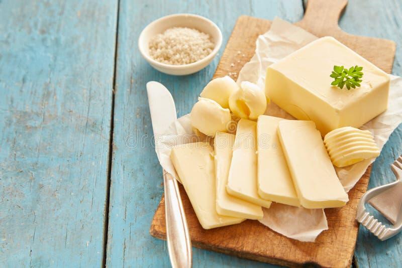 Blok van boter op houten scherpe raad wordt gesneden die royalty-vrije stock afbeeldingen