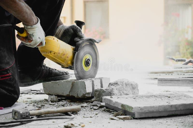 Blok van het arbeiders het scherpe kalksteen met de zaag van het machtshulpmiddel royalty-vrije stock afbeelding