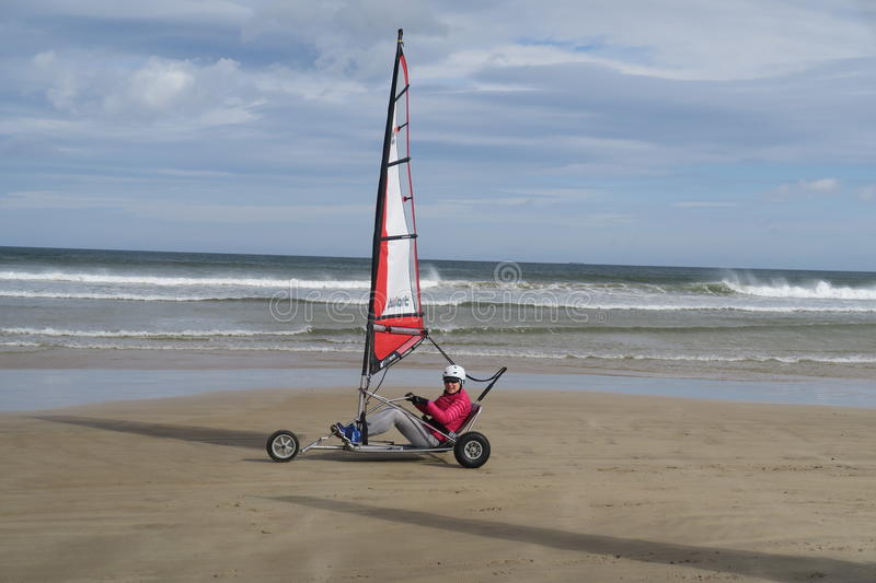 Blokart. A small cart with a sail that you can steer along the beach on three wheels. blokart has developed into a culture with an international community of stock photos
