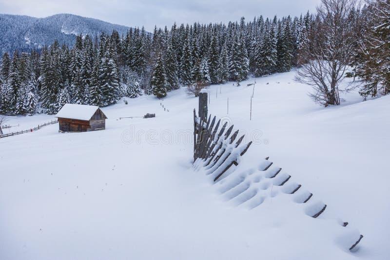 Blokhuis in een perfect sneeuw de winterlandschap De sneeuw behandelde landelijk en boslandschap royalty-vrije stock afbeeldingen