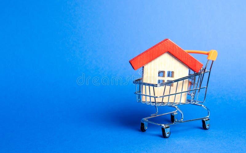Blokhuis in een Supermarkt handelkar Het concept het kopen van een huis of een flat Betaalbare huisvesting Voordelig en goedkoop stock afbeeldingen
