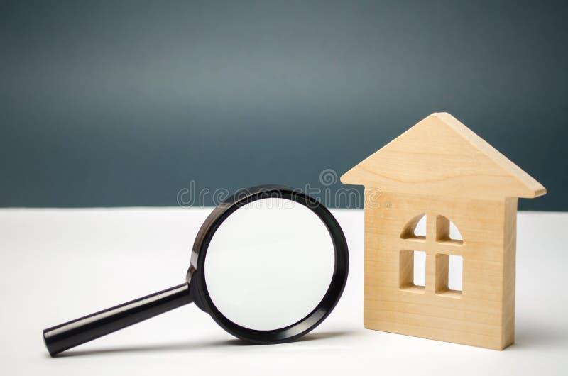 Blokhuis en vergrootglas Bezitswaardevaststelling Keus van plaats voor de bouw Huis die concept zoeken zoek stock afbeelding