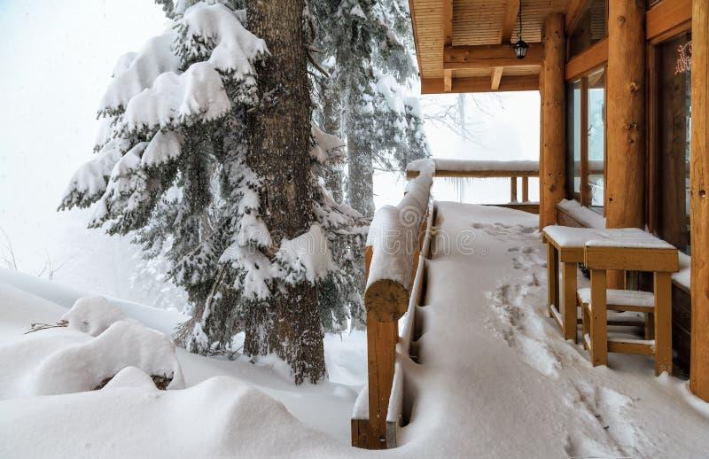 Blokhuis in het bergbos bij de sneeuwwinter tijdens hard sneeuwstorm mistig toneellandschap royalty-vrije stock afbeeldingen