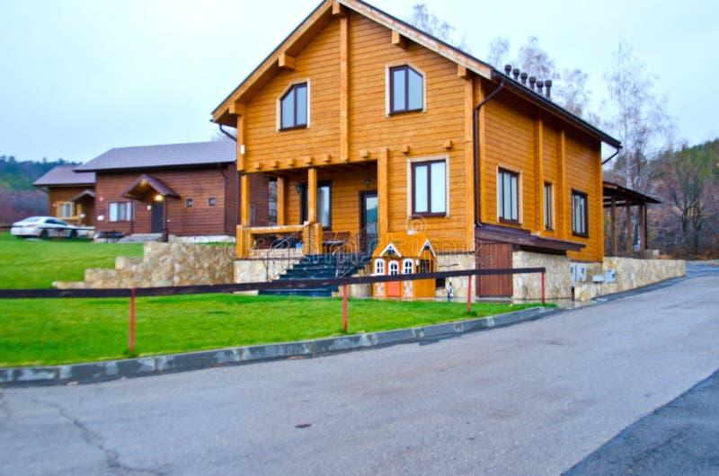 Blokhuis, het plattelandshuisje naast het gazon en de weg stock afbeelding