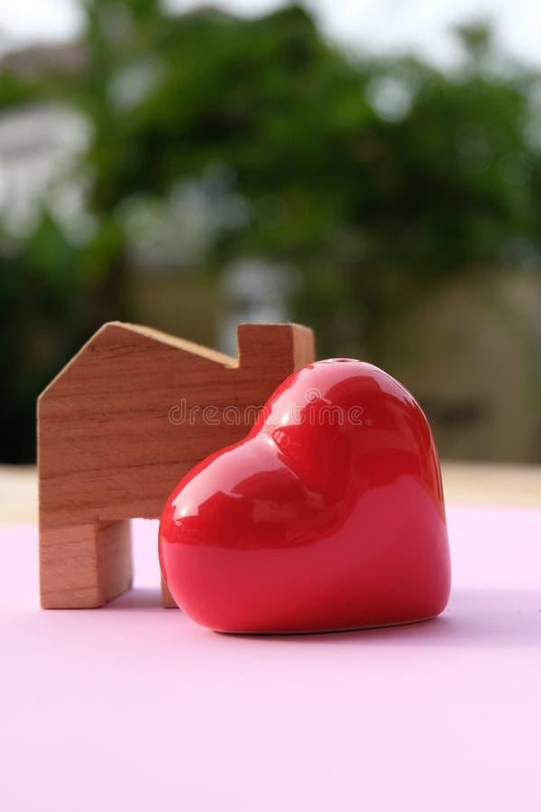 Blokhuis modeltribune opzij van groot rood hart Gelukkig huis en familieconcept Het concept van de liefde stock fotografie