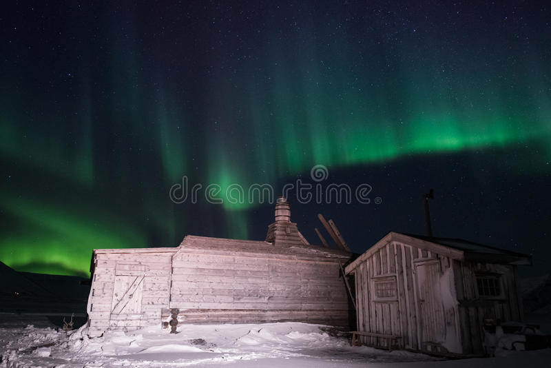 Blokhuis, yurt hut op de achtergrond de polaire Noordelijke aurora borealislichten stock foto's