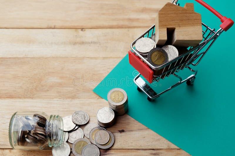 Blokhuismodel op boodschappenwagentje met muntstukken die van de glaskruik wegvloeien Kopend huis, huishypotheek, bezitsinvesteri royalty-vrije stock afbeeldingen