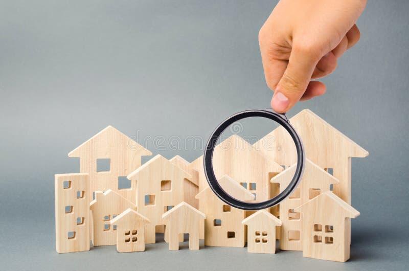 Blokhuizen en vergrootglas Bezitswaardevaststelling Huisschatting Keus van plaats voor de bouw Huis het zoeken stock fotografie