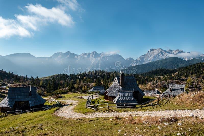 Blokhuizen in Velika Planina met alpen in backround stock foto