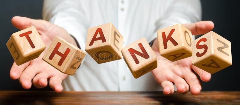 Bloki rzucone przez człowieka z literami od słowa Dziękujemy Osoba dziękuje i docenia służbę lub pomoc zdjęcie royalty free