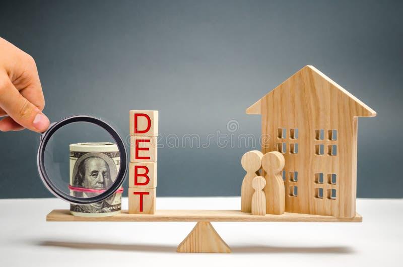 Blokken met de het woordschuld en geld, familie en blokhuis Onroerende goederen, huisbesparingen, het concept van de leningenmark royalty-vrije stock foto's