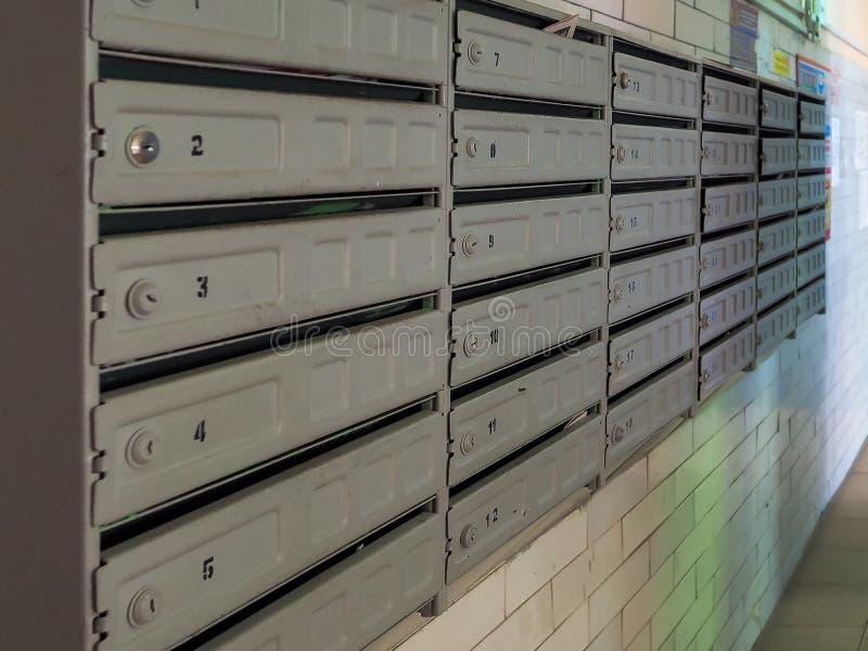 Blokowe skrzynki pocztowe w wejściu stary budynek mieszkaniowy W oczekiwaniu na kwit korespondencja fotografia royalty free