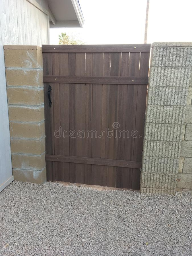 Blokowy ogrodzenie z niedawno zainstalowaną brown drewnianą bramą fotografia stock