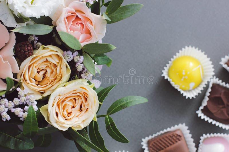 Blom- bukett och godis i bakgrunden fotografering för bildbyråer