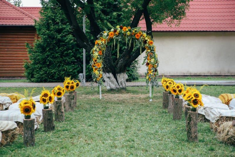 Blom- lantlig båge för bröllopceremoni med solrosor royaltyfri bild