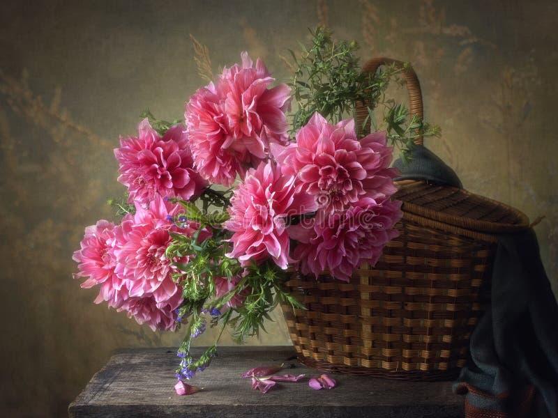 Blom- stilleben för sommar med härliga bukettdahlior i en korg arkivbilder