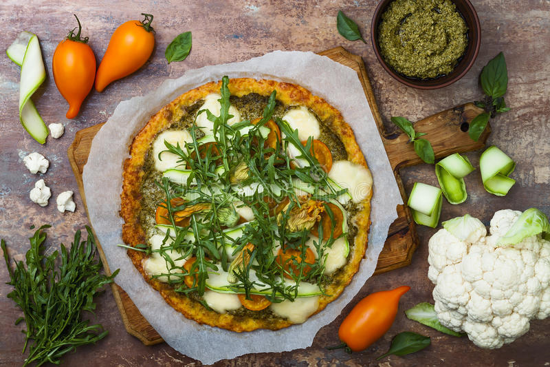 Blomkålpizzaskorpan med pesto, gula tomater, zucchinin, mozzarellaost och squash blomstrar arkivbild