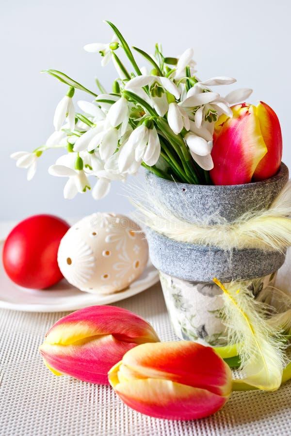 Blomkrukan med vita snödroppar och tulpanblommor och dekorerad vit perforerade ägg på den vita bakgrunden royaltyfri foto