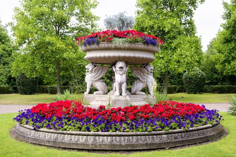 Blomkrukan som stöttas av stenen påskyndade lejon i regenter, parkerar royaltyfri fotografi