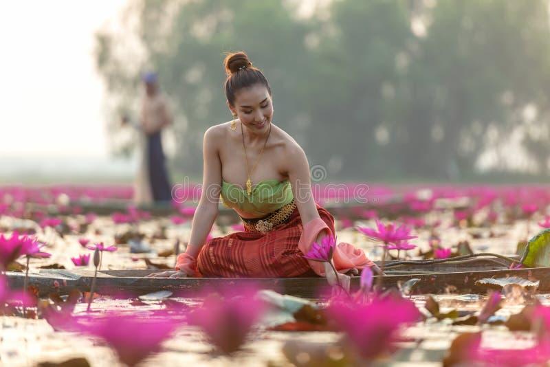 Blomma för lotusblomma för traditionell asiatisk kvinnaskörd röd på fartyget i naturfloden, arkivbilder