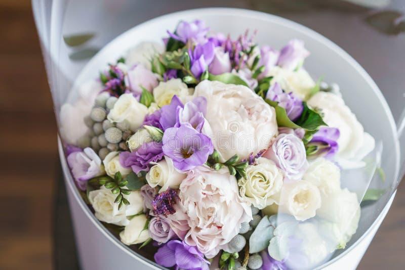 Blomma i genomskinlig plast- ask Brudar som gifta sig buketten med pioner, freesia och andra blommor på svart armstol royaltyfria bilder