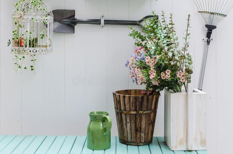 Blomma på grön bänk med den vita wood panelväggen i trädgård royaltyfria foton
