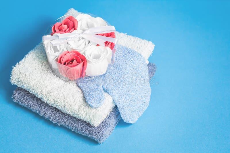 Blommabadtvål bombarderar och två handdukar på blå bakgrund fotografering för bildbyråer
