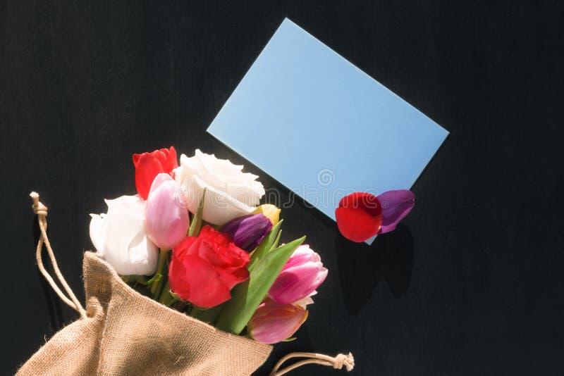 Blommabukett och meddelandekort med kronblad royaltyfria bilder