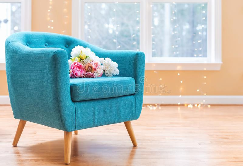 Blommabuketter i lyxhem med turkosstol arkivfoton