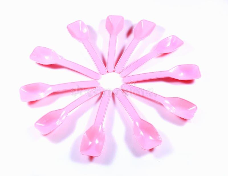 Blomman format lager av rosa färgfärgplast- behandla som ett barn skedar arkivbild