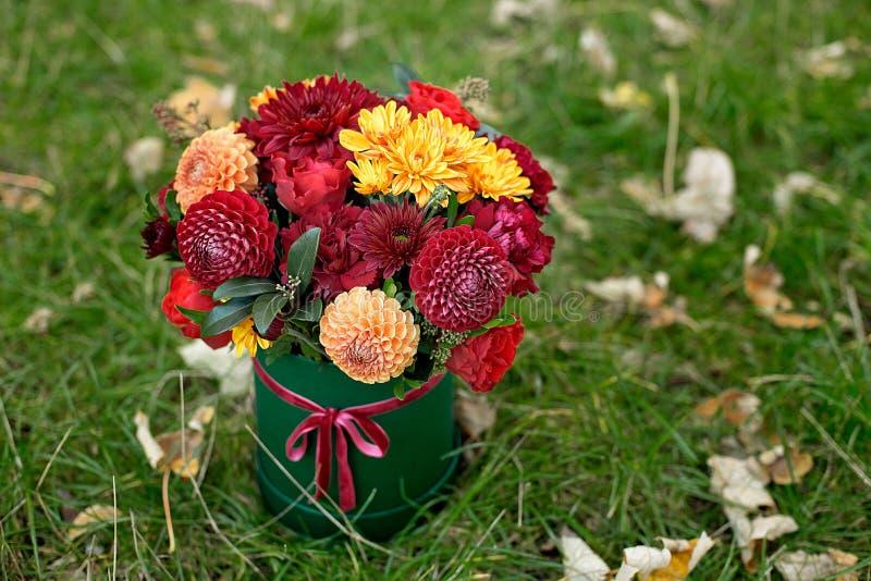 Blommaordning i en ask, en kruka med rosa, rött, apelsin, marsala för en flicka som en gåva med rosor, aster, freesia royaltyfri fotografi