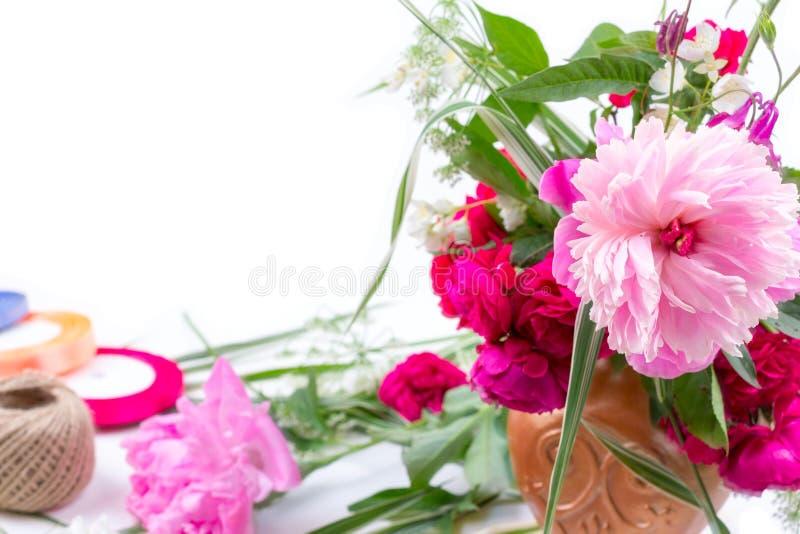 Blommaordning med en härlig bukett av rosa pionblommor, blåklinter och röda rosor på en vit bakgrund med utrymme för arkivfoton