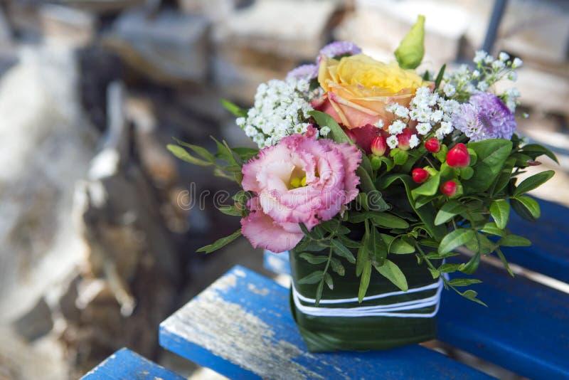 Blommaordning på en trästol arkivfoto