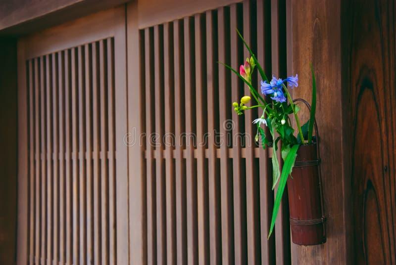 Blommaordning utanför japanska dörrar royaltyfri foto