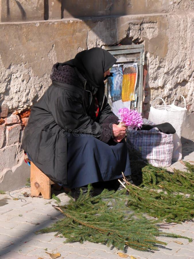 blommar den gammala säljande kvinnan royaltyfria foton