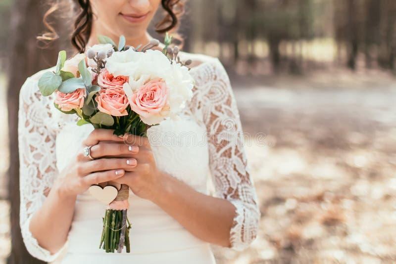 Blommar den hållande bröllopbuketten för bruden med rosor och annan arkivbild