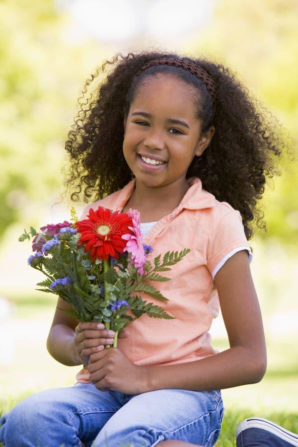 blommar flickaholdingbarn arkivfoton