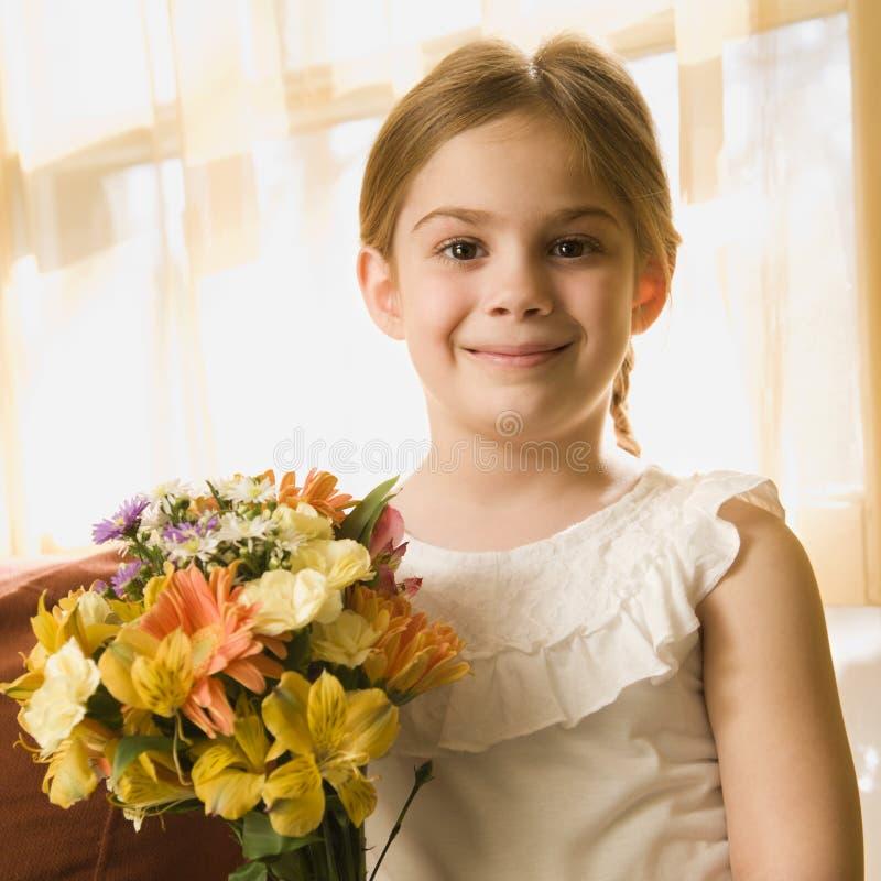 blommar flickaholdingen royaltyfria foton